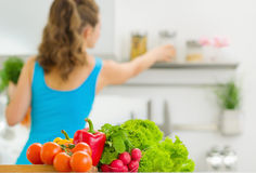 Closeup on vegetable and housewife in background Stock Photos