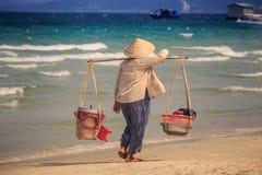 Closeup Vendor Woman with Yoke Walks along Beach against Sea Royalty Free Stock Image
