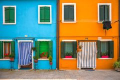 Closeup of vibrant colorful houses in Burano island, Italy. Burano house with striped curtains on front door in summer Stock Photography