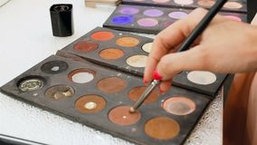Closeup video of colorful palette with paints and shadows for makeup. Professional makeup artist or visagiste holding stock video footage