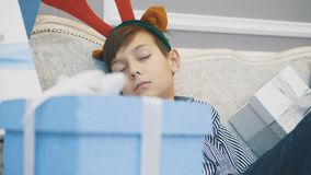 Closeup video of little boy with reindeer antlers on head, sleeping on the sofa among Christmas presenst. Blurred