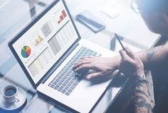 Closeup view of adult tattooed businessman working on mobile computer at sunny office.Man typing on notebook keyboard. Graphs and diagramm on laptop screen royalty free stock image