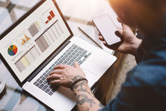 Closeup view of adult tattooed coworker holding smartphone on hand and using laptop while working at sunny office.Graphs. And diagramm on notebook screen royalty free stock photo