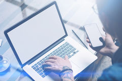 Closeup view of adult tattooed coworker holding smartphone on hand and using laptop while working at sunny office.White. Blank notebook screen.Blurred stock images