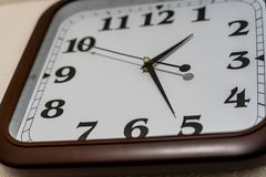 Closeup view of Analog Clock on the Wall with Brown Frame. Concept of Deadline and Business Hours stock images