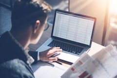 Closeup view of banking finance analyst in eyeglasses working at sunny office on laptop while sitting at wooden table. Businessman analyze stock report on stock images