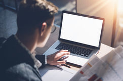 Closeup view of banking finance analyst in eyeglasses working at sunny office on laptop while sitting at wooden table. Businessman analyze stock report on royalty free stock images