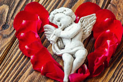 Closeup view of beautiful cupid with the trumpet, angel decorative figurine near red rose petals on wooden background. Royalty Free Stock Images