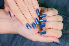 Female hands with blue glossy professional manicure stock image