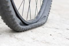 Bicycle wheel with flat tyre on the concrete road. Royalty Free Stock Photo