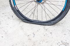 Bicycle wheel with flat tyre on the concrete road. Stock Photography