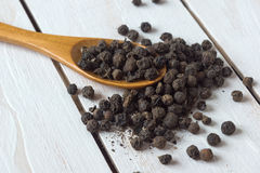 Closeup view of black pepper corns and spoon Stock Image