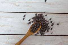 Closeup view of black pepper corns and spoon on wooden background Royalty Free Stock Photography