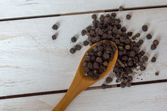Closeup view of black pepper corns and spoon on wooden background Royalty Free Stock Images