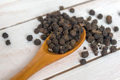 Closeup view of black pepper corns and spoon on wooden background Royalty Free Stock Image