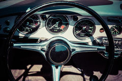 Closeup view of a black steering wheel and a dashboard Royalty Free Stock Photos