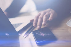 Closeup view of businessman pointing finger on smartphone screen.Elegant coworker working at sunny office on laptop. Blurred background.Horizontal royalty free stock images