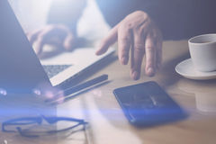 Closeup view of businessman pointing finger on smartphone screen.Elegant coworker working at sunny office on laptop at. The wooden table.Blurred background royalty free stock images