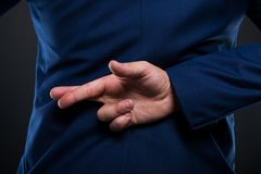 Closeup view of businessman standing with crossed fingers. Closeup view of liar businessman standing with crossed fingers behind his back Royalty Free Stock Photos