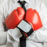 Businessman wearing red boxing gloves. Closeup view of businessman wearing red boxing gloves with his arms crossed on his chest royalty free stock images