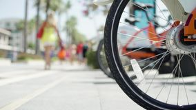 Closeup view of bycicle wheel in sharing point. With unrecognizable people on background stock video