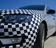 Closeup view of the car checkerboard pattern with detail headlight and rearview mirror. With blue sky Stock Photography