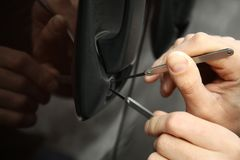 Closeup view of carjacker trying to open car. With pick-lock Stock Image