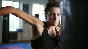 Closeup view of caucasian female boxer hitting the boxing bag with her hands in gloves in the gym alone. Tough power. Training of a female kickboxer stock video