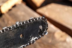 Closeup view of a chainsaw bar and cutting chain. Dirty blade of a chainsaw. Blade of a chainsaw in the garden, copy space. Royalty Free Stock Images