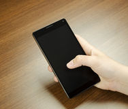 Closeup view of a child hand with fingers holding a black cell phone with black screen on wooden mat blur Royalty Free Stock Photos