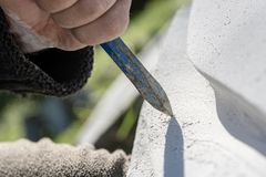 Closeup view of chisel as sculptor works. And carves in stone stock image