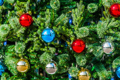 Closeup view of a Christmas tree decorated with glass balls of r Royalty Free Stock Photo