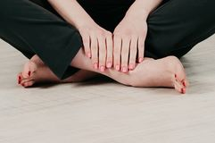 Closeup view of a cross-legged girl on the floor, pink manicure royalty free stock images