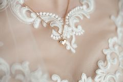 Ute small romantic golden heart hanging on necklace chain. Closeup view of cute small romantic golden heart hanging on necklace chain on breast of young bride Stock Image