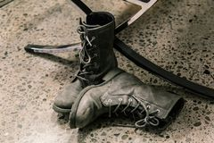 closeup view of dark grey pair of stylish boots, man`s wear on dark concrete floor Royalty Free Stock Images