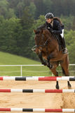Closeup view of dark haired horsewoman jumping Stock Images