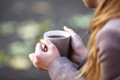 Closeup view of disposable cup of coffee or tea in womans hand. Royalty Free Stock Image