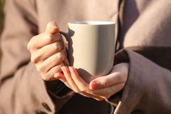 Closeup view of disposable cup of coffee or tea in womans hand. Royalty Free Stock Photo
