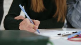 Closeup view of diverse multi-ethnic students writing an exam at school or university. Test at school. Slowmotion shot.  stock footage