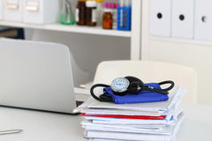 Closeup view of doctor working table. Laptop, manometer and heap of documents lying on desktop, Physician office. Healthcare and medical concept Stock Photos