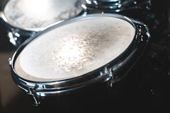 Closeup view of a drum set in a dark studio. Black drum barrels with chrome trim. The concept of live performances.  royalty free stock image