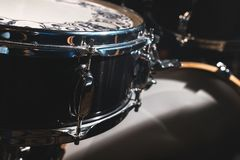 Closeup view of a drum set in a dark studio. Black drum barrels with chrome trim. The concept of live performances.  royalty free stock photo