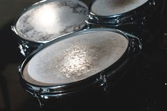 Closeup view of a drum set in a dark studio. Black drum barrels with chrome trim. The concept of live performances.  stock photography