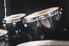 Closeup view of a drum set in a dark studio. Black drum barrels with chrome trim. The concept of live performances.  royalty free stock images