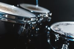 Closeup view of a drum set in a dark studio. Black drum barrels with chrome trim. The concept of live performances.  royalty free stock photos