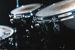 Closeup view of a drum set in a dark studio. Black drum barrels with chrome trim. The concept of live performances.  stock image