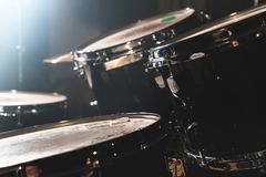 Closeup view of a drum set in a dark studio. Black drum barrels with chrome trim. The concept of live performances.  stock images