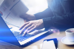 Closeup view of Elegant businessman working at sunny office on laptop computer while sitting at the wooden table.Man. Holding paper reports in hands.Blurred royalty free stock photography