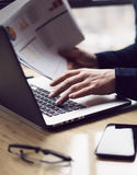 Closeup view of Elegant businessman working at sunny office on laptop computer while sitting at the wooden table.Man. Holding paper reports in hands.Blurred royalty free stock image