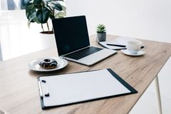 Closeup view of empty clipboard, doughnut, coffee cup, potted plant, textbook and laptop. On wooden table royalty free stock photos